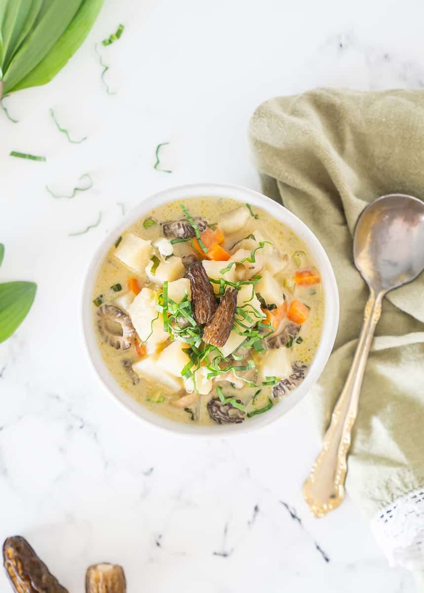 Morel Ramp Potato Chowder in a white bowl on a marble background