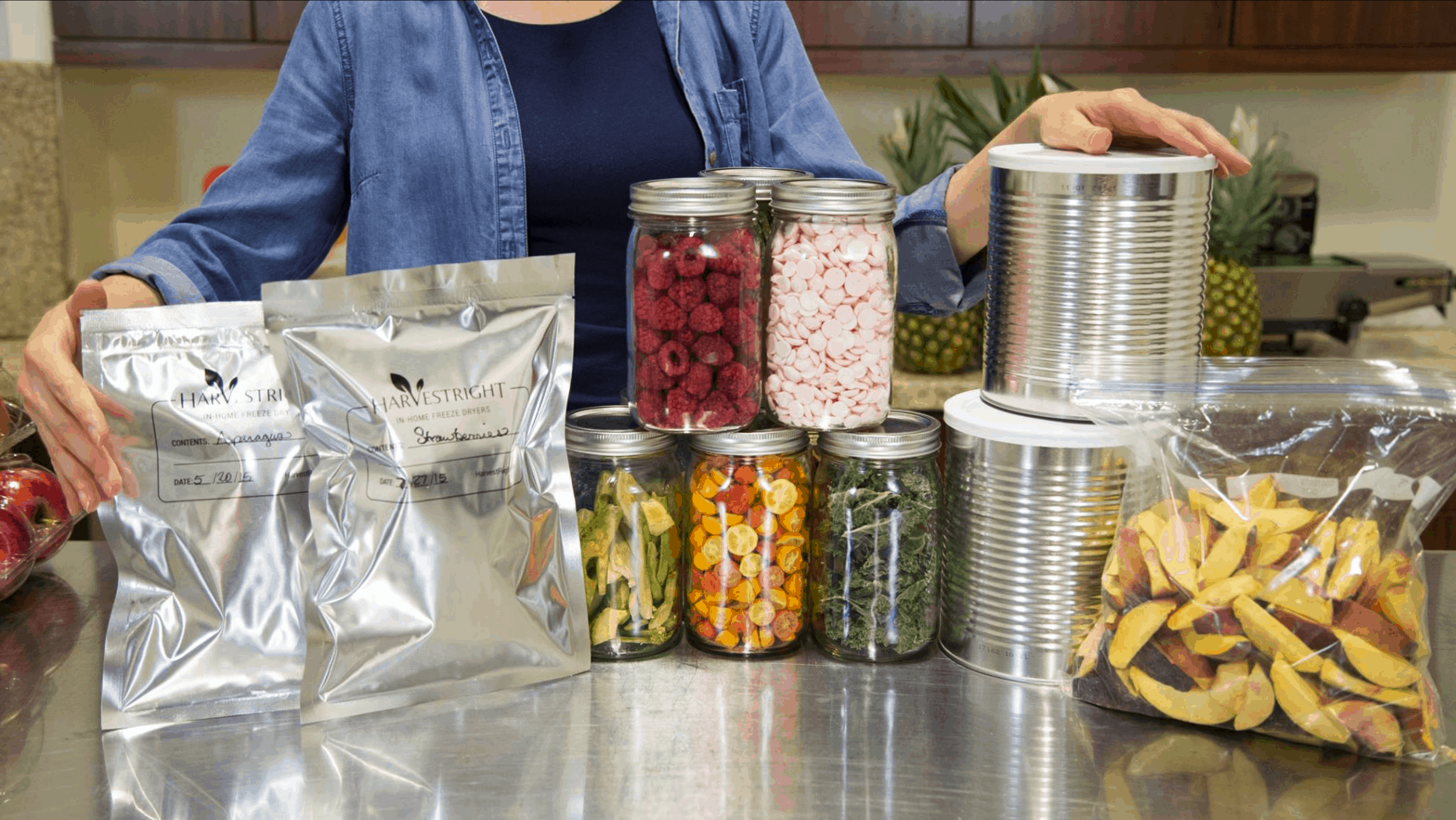 woman standing behind an assortment of freeze dried foods