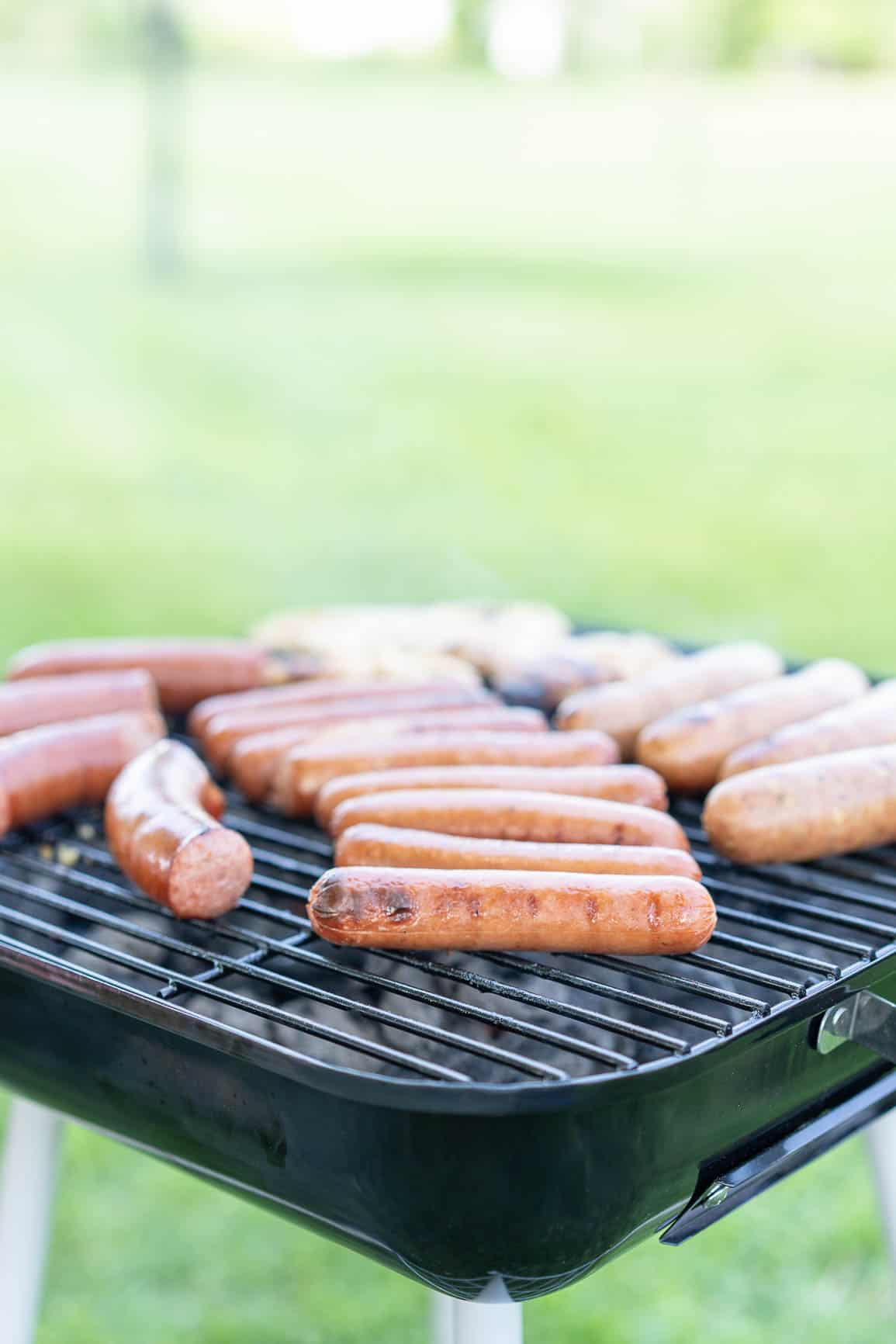 Charcoal grill with hot dogs, kielbasa, sausage and chicken on it.
