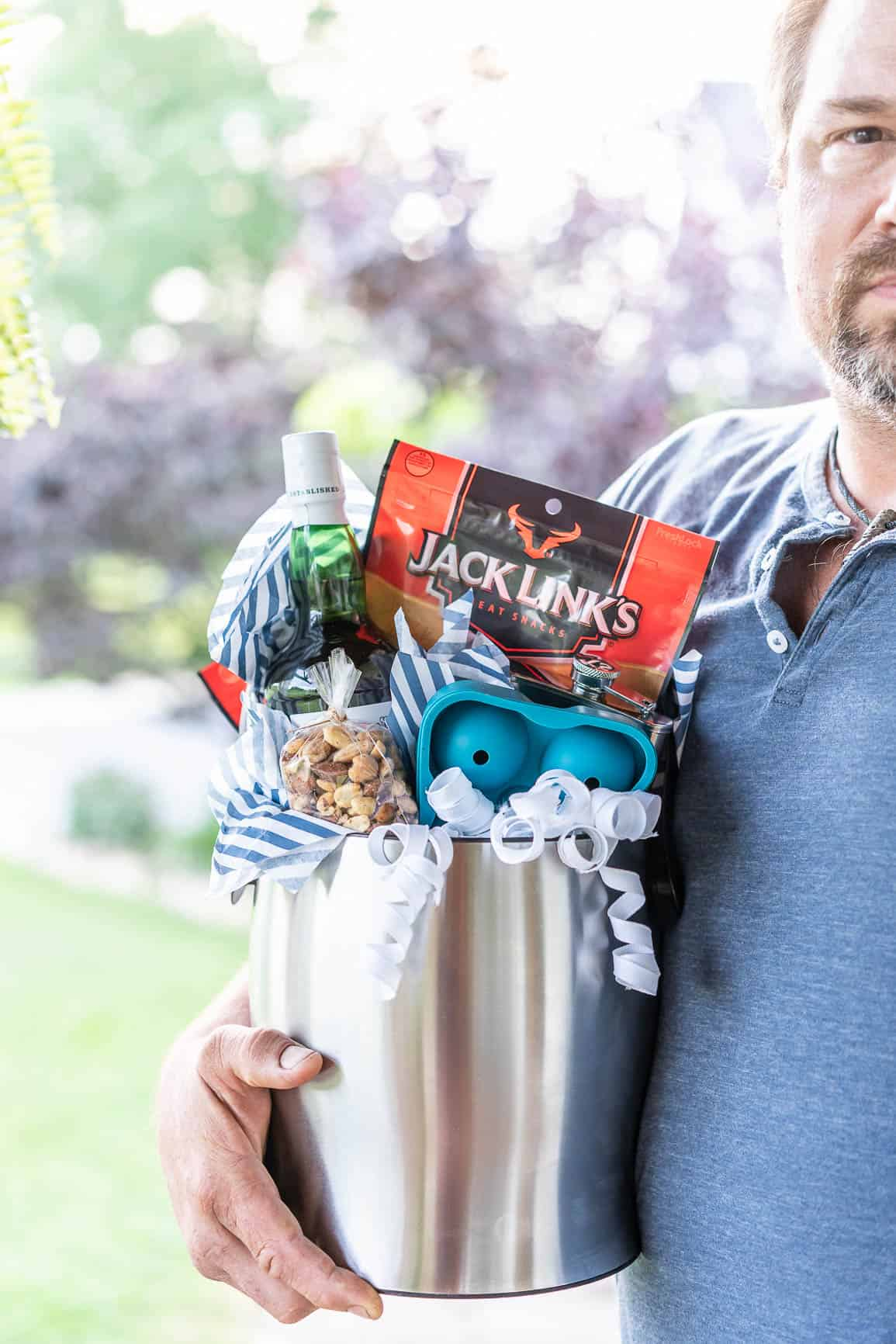 man holding a gift basket with scotch whiskey drinking items.