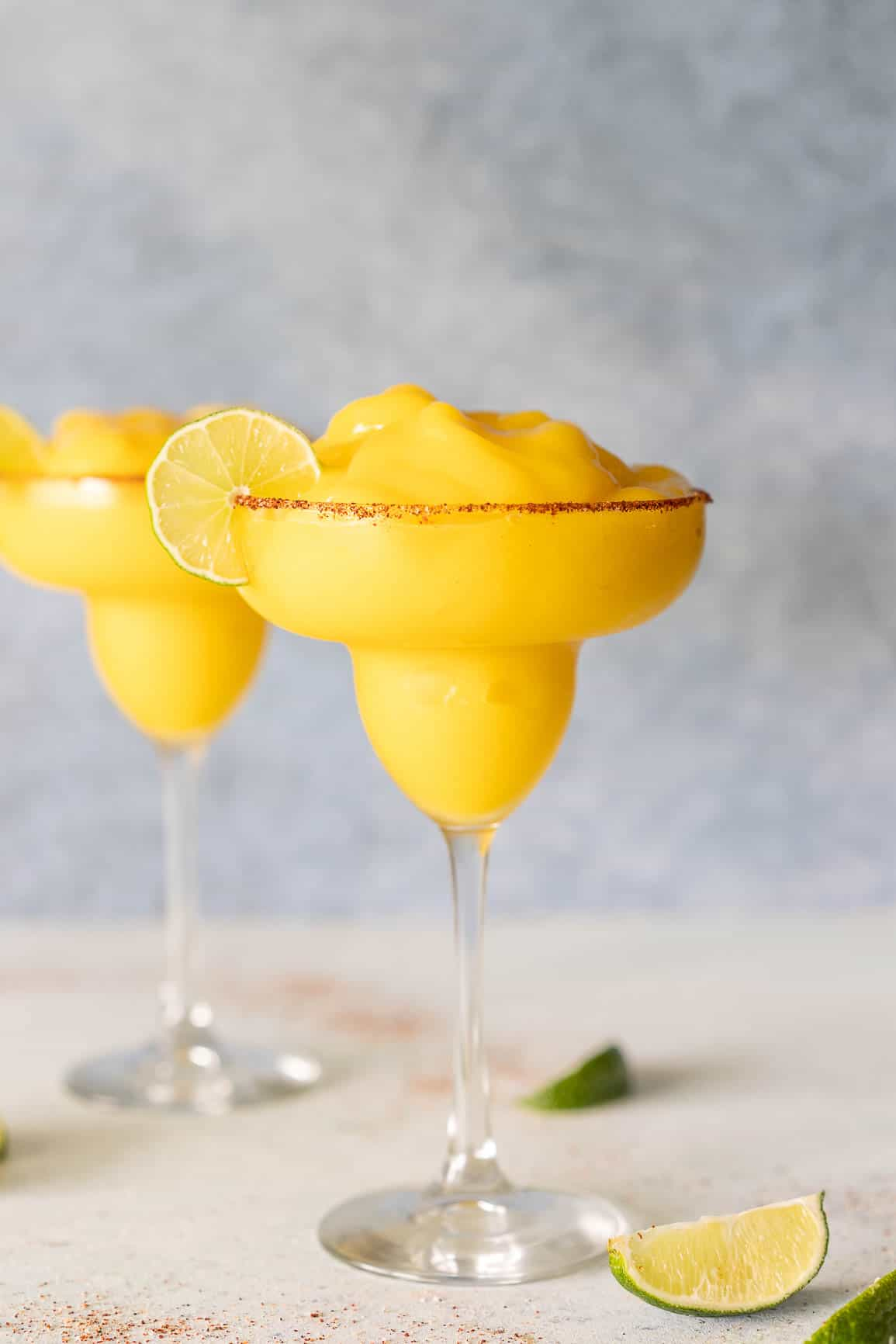 bright orange frozen mango margarita in a glass rimmed with chili lime seasoning.