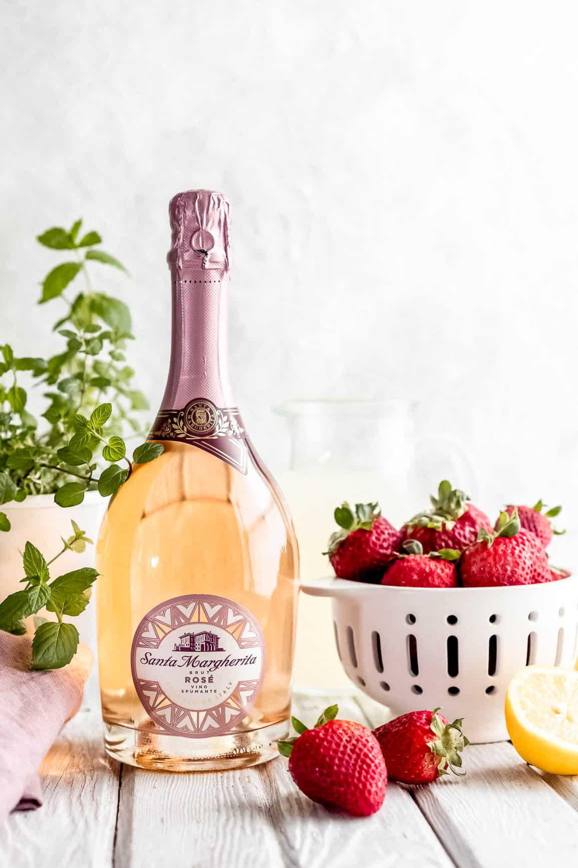 Santa Margherita Sparkling Rose with potted mint and colander of fresh red strawberries.