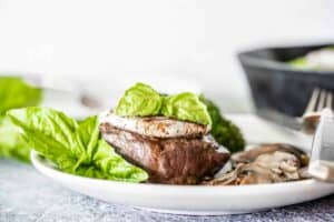 Petite filet topped with goat cheese and basil on a white plate