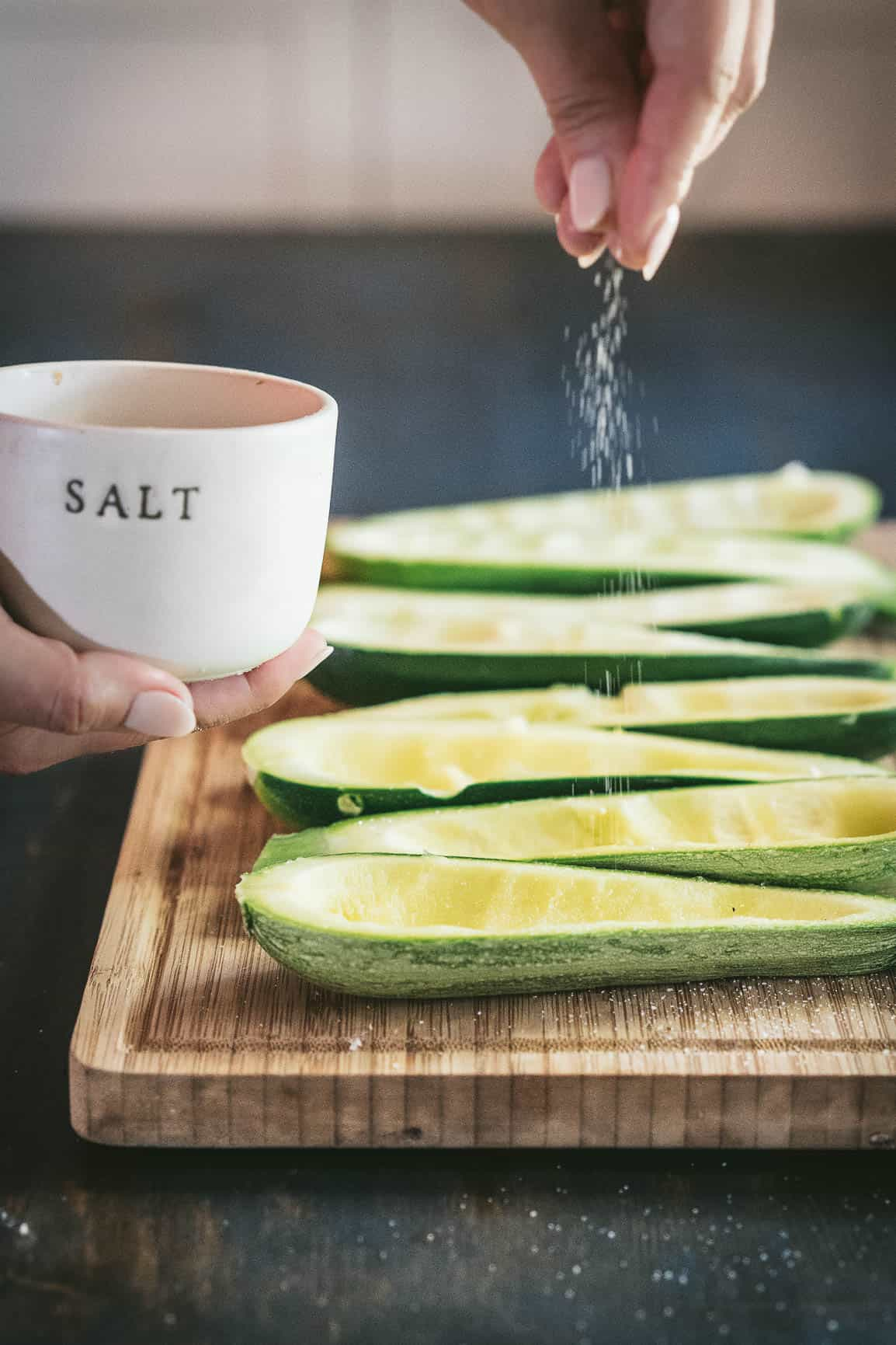 zucchini halves with the seeds scooped out to make boats on a wooden cutting board with a hand above sprinkling sea salt.