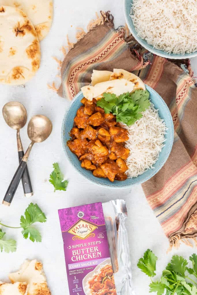 naan bread, brass spoons, striped napkin and bowl of butter chicken with rice garnished with fresh cilantro.