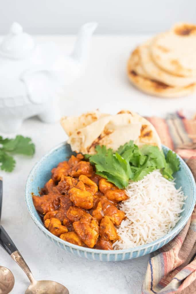 blue bowl of butter chicken with rice, cilantro and naan bread