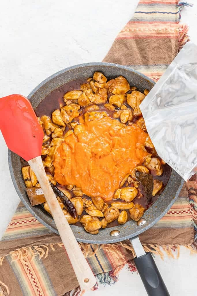 cooking Indian butter chicken in a grey skillet with a red spatula with wooden handle.