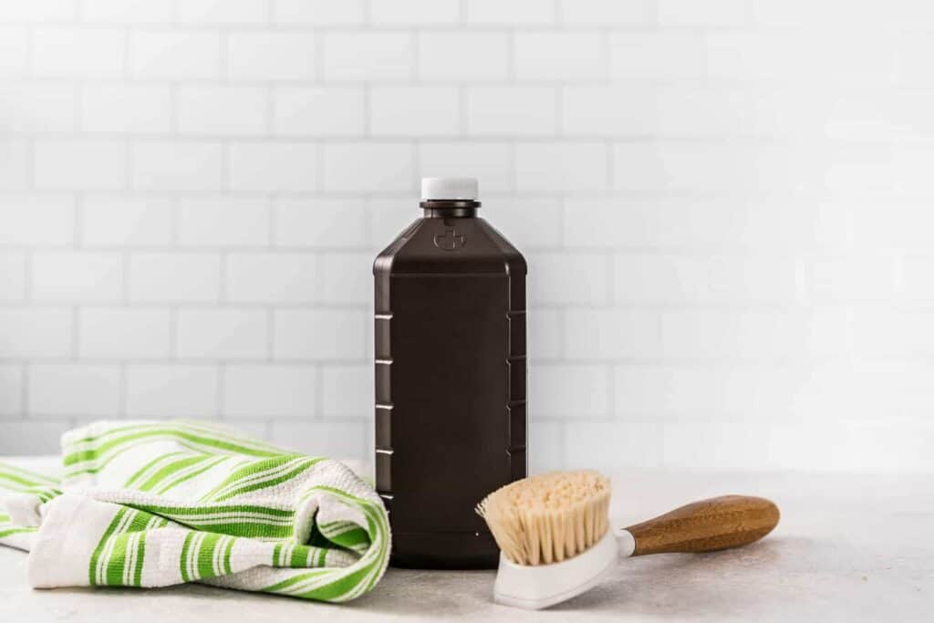 Bottle of hydrogen peroxide in front of a white subway tile wall with green stripe kitchen towel and cleanign brush