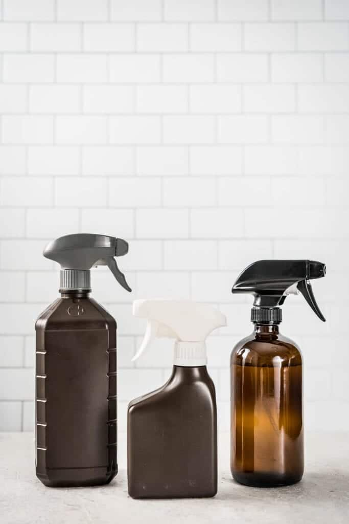 3 brown spray bottles in front of a white subway tile wall with gray grout