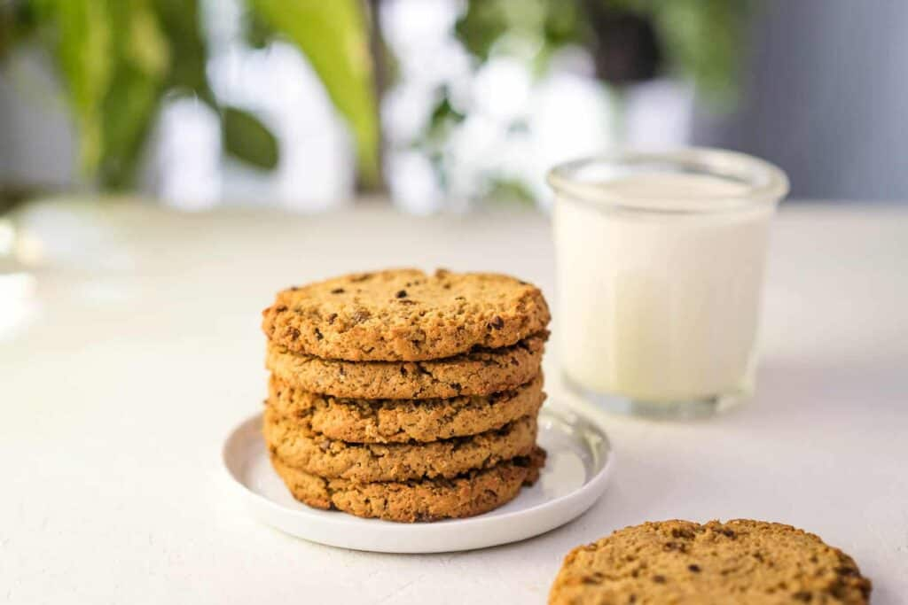stack of 5 chocolate chip cookies with a cookie in the front with a bite taken out, glass of milk in the background