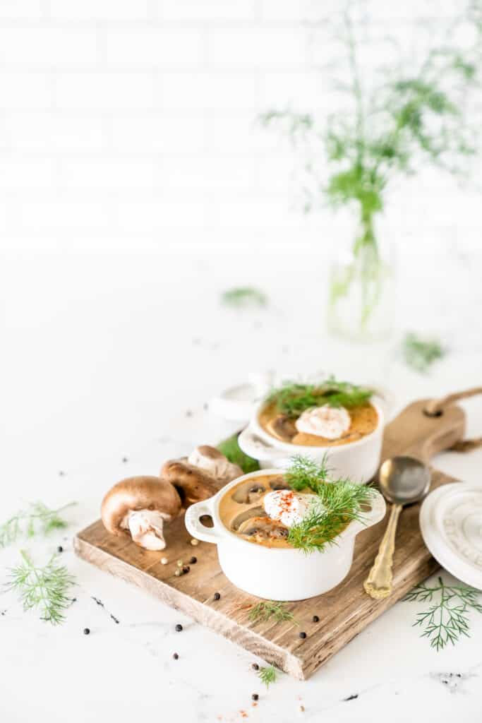 Hungarian mushroom stew in white bowls with fresh dill