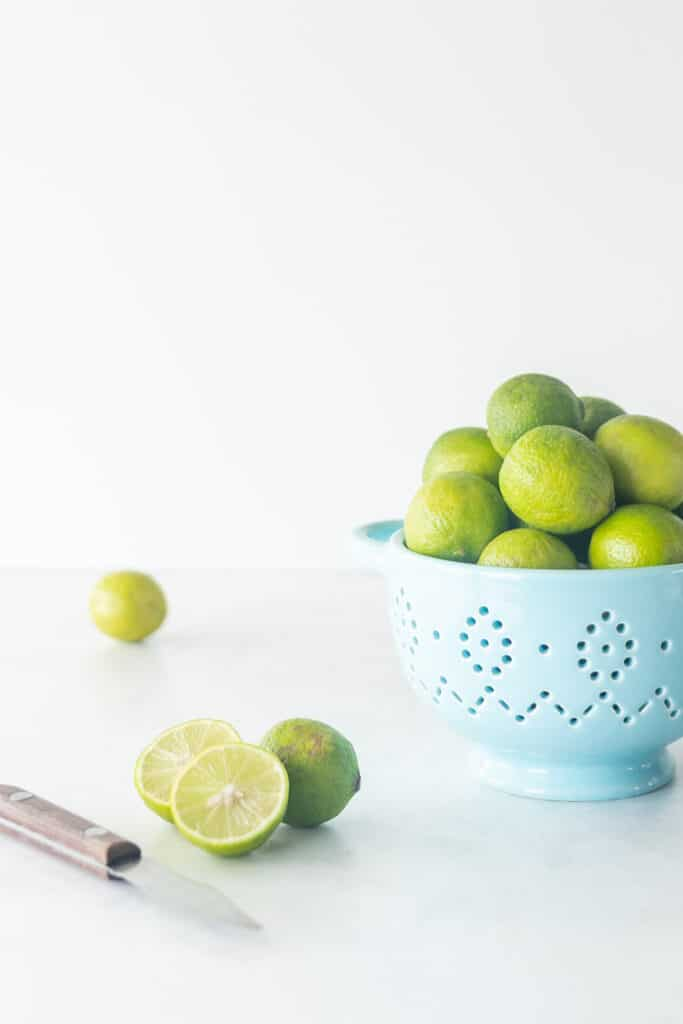 Key limes in blue colander with old knife on the side