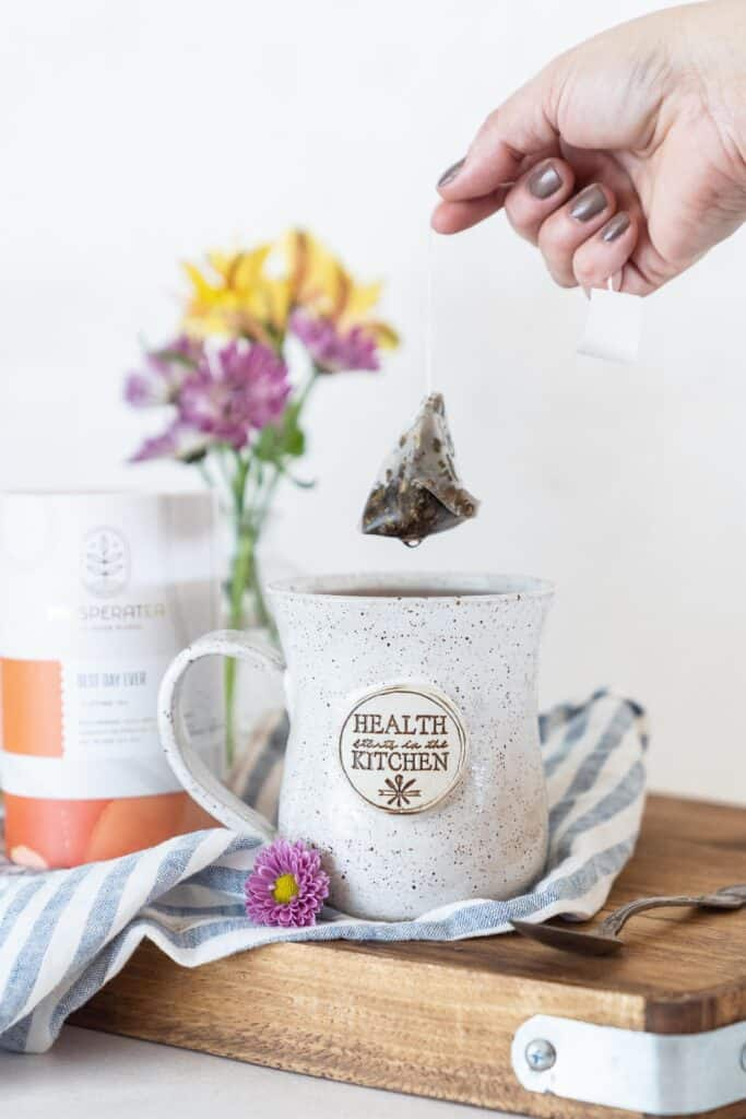 handmade mug with stamped with health starts in the kitchen, filled with tea, teabag held above