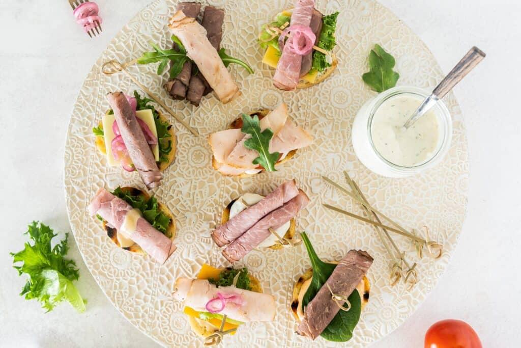 crostini sandwich bites on a decorative tray