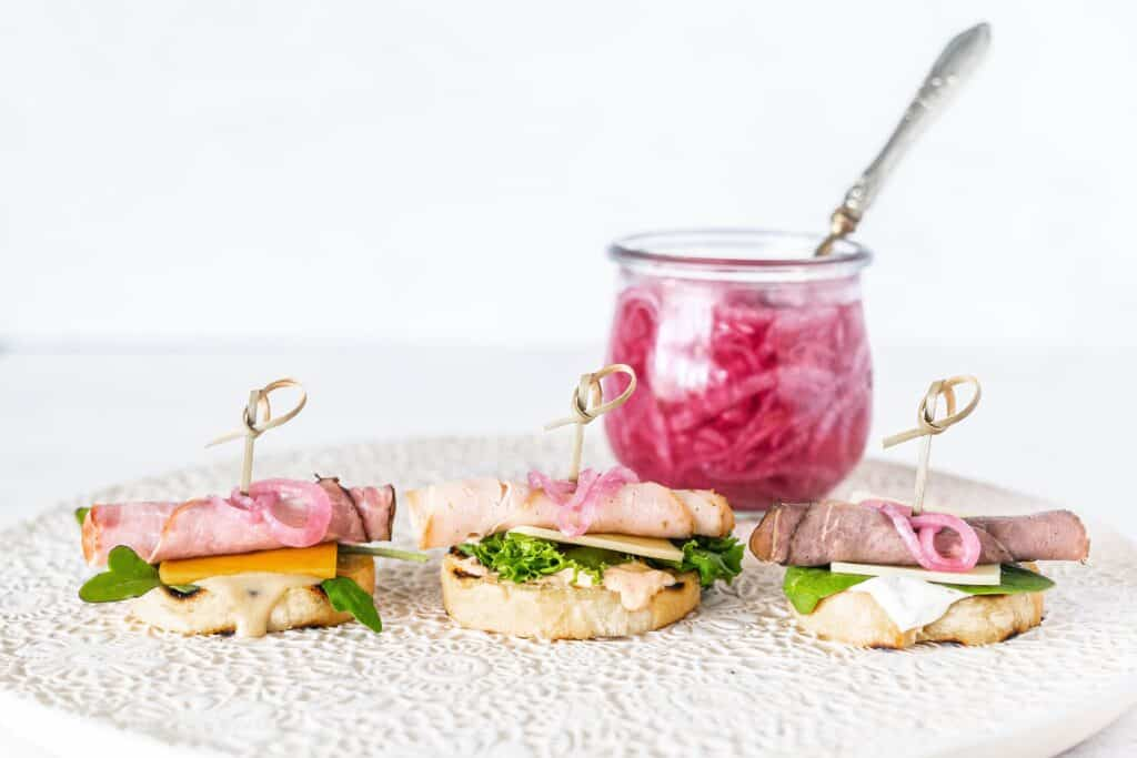 3 crostini sandwiches on a platter with pickled red onion in the background