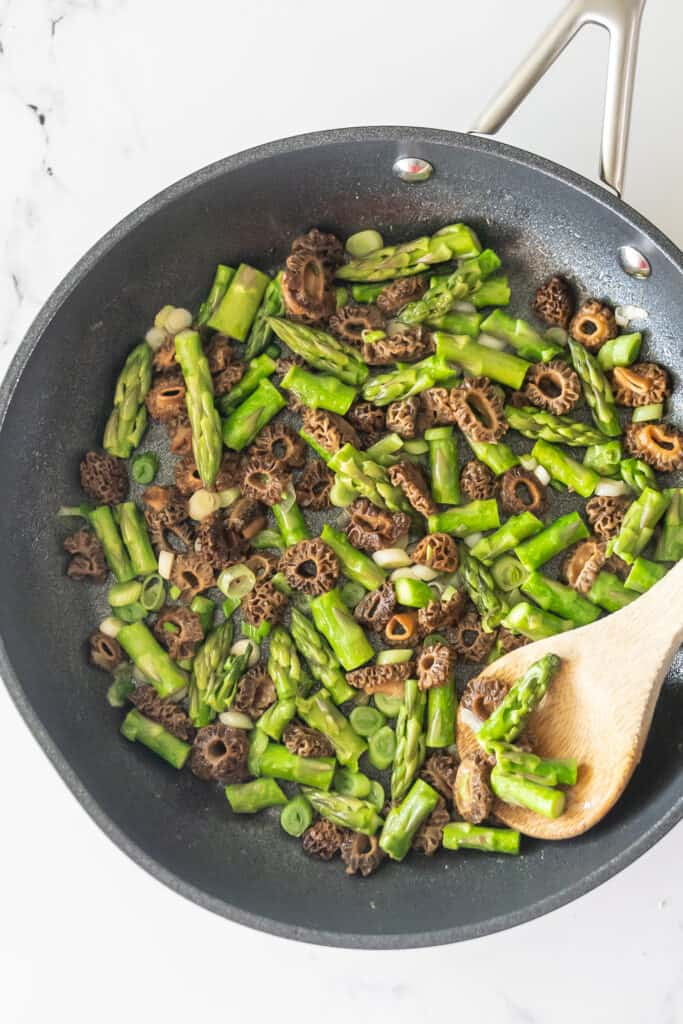 morel mushrooms, onions and asparagus in a skillet