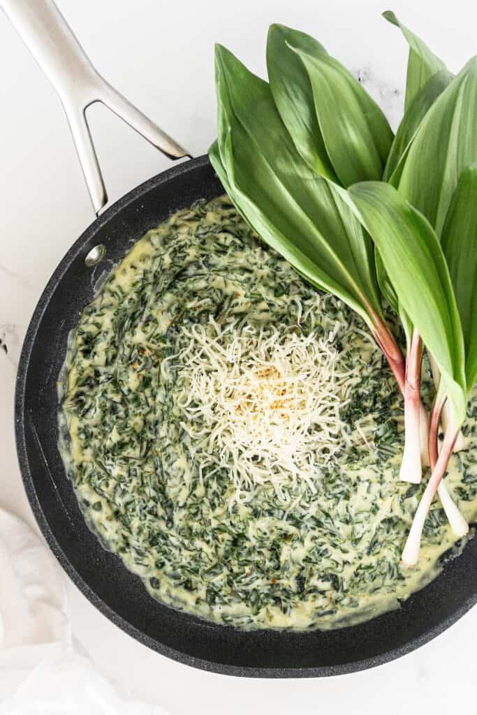 Creamed Ramp Greens in a non stick skillet, garnished with shredded cheese and fresh whole ramps