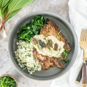 gray background with a gray bowl, holding sautéed green, rice and pork chops topped with a parmesan sauce with ramps and morels