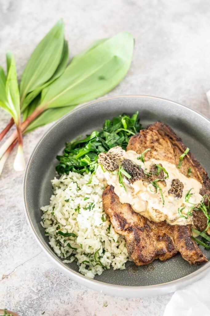 a grey bowl with ramp rice, sautéed ramp greens and a pork chop topped with morel mushroom ramp cream sauce