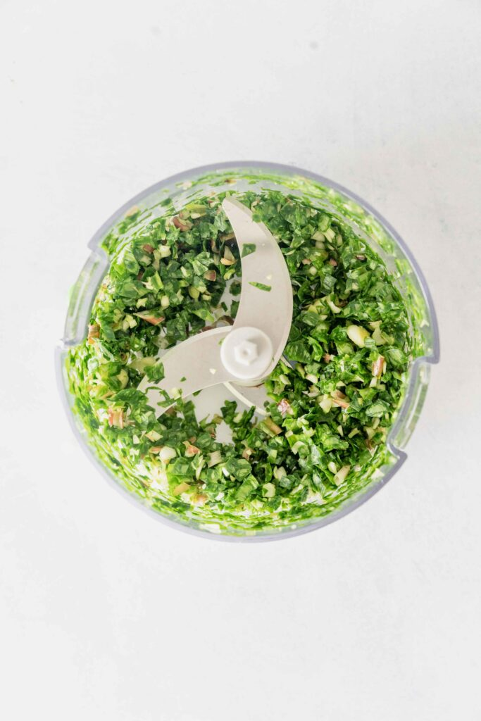 base of a mini food processor filled with finely chopped ramps
